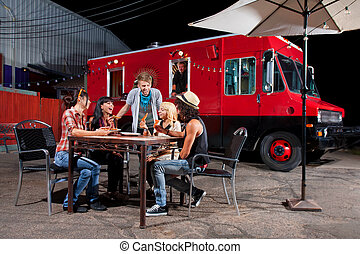 Eating Pizza Near Food Truck - Laughing friends at food...
