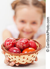 Happy girl holding easter eggs in a basket