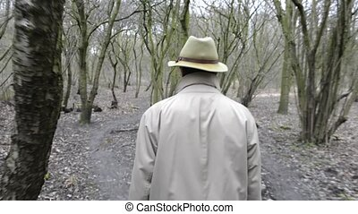 Walking through the woods - Man, wearing a khaki rain coat...