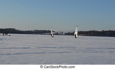 sailer winter ice surfer - follow two ice surfers men...