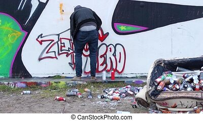 Graffiti Artist - Graffiti artist at work behind an upturned...