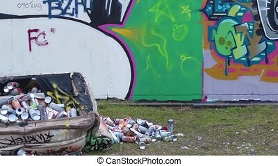 Graffiti wall and artist - Pan over a graffiti wall, towards...