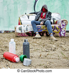 Graffiti paint - Spray paint cans on the sand in front of a...