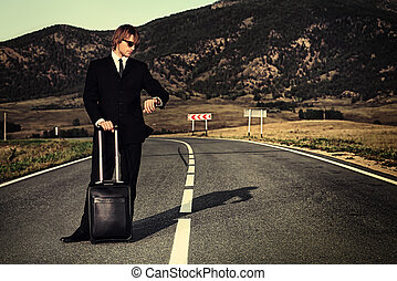 time concept - Handsome business man standing on a highway...