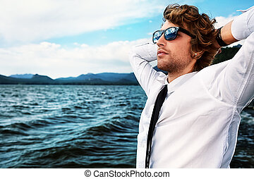 trip business - Handsome business man standing on a seaside...