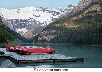 Row of canoes, Banff National Park - Row of red canoes,...