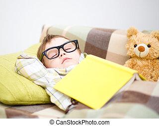 Cute little boy is sleeping in front of his teddy bears...