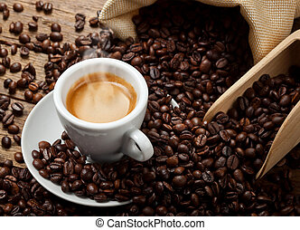 Espresso - Coffee cup with burlap sack of roasted beans on...