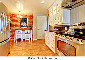 White kitchen with brick wall, hardwood and stainless steal stove.