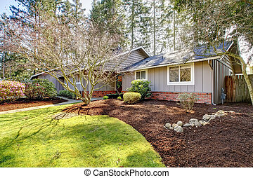 Brown grey house exterior with spring landscape. One story...