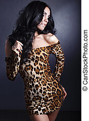 fashion portrait sexy brunette girl in a leopard dress