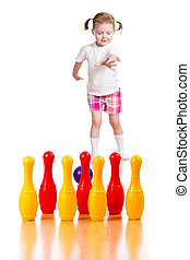 Kid girl throwing ball to knock down toy bowling pins. Focus...