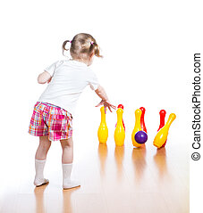 Kid throwing ball to knock down toy bowling pins. Focus on...