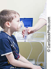Close up image of a little boy with asthma using oxygen mask...