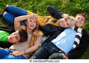 Group of four young people laying in the grass