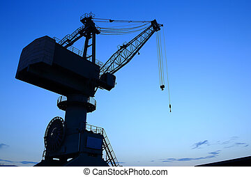 Cranes in dockyard at sunset