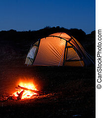 illuminated tent and campfire - tent glows at night with...