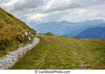 Foot path in a mountainous landscape a cloudy day in...