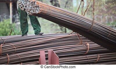 Construction worker loading steel
