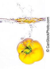 yellow paprika pepper splashes into water before white