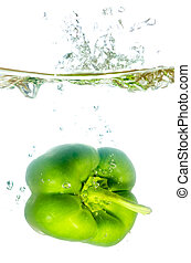 green paprika pepper splashes into water before white