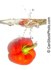 red paprika pepper splashes into water before white