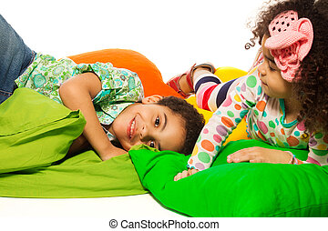 Black boy and girl playing with pillows