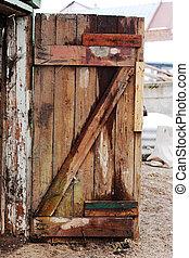 Old decayed wooden door. Door made of discoloured pine...