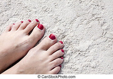 Feet on sand - Woman feet with red toenails on natural beach...