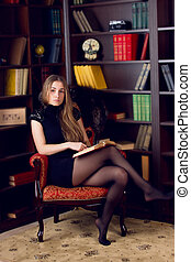 girl in the home library - Clever young woman sits on couch...