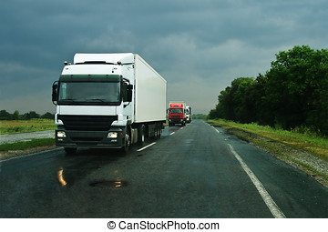 Trucks on wet asphalt - Group of trucks on wet asphalt after...