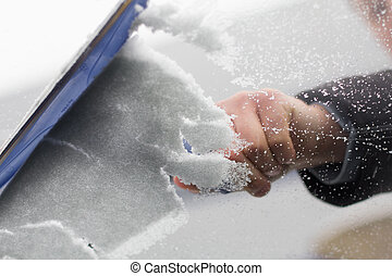 A man cleans snow from windshield