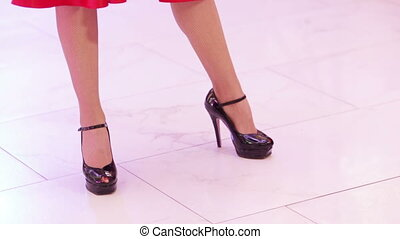 Dancing womans legs - Girl standing on a white floor and...