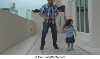 Young girl dancing with her father