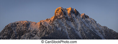 red lighted peak of austrian mountain at sunset in winter