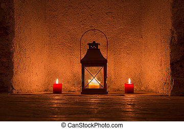 vintage candlelit in metal lantern standing in stone wall...