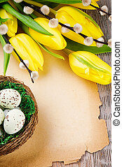 Easter frame with tulips and vintage paper on wooden table