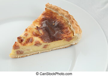 Fresh baked slice of quiche lorraine on a plate