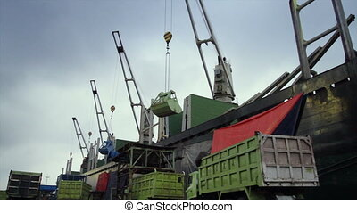 unloading activity at ship yard - cranes unloading activity...