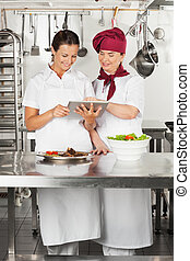 Chefs Using Digital Tablet In Kitchen - Two female chefs...