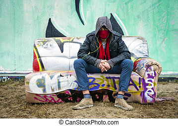 hooded graffiti artist - Young man with an attitude sitting...