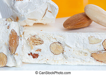 Sweet nougat with almonds on white background