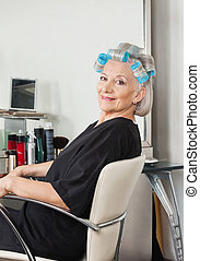 Woman With Hair Curlers Sitting On Chair At Salon