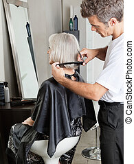 Woman Getting Hair Cut In Beauty Parlor - Senior woman...
