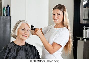 Hairdresser Ironing Customer's Hair - Portrait of female...