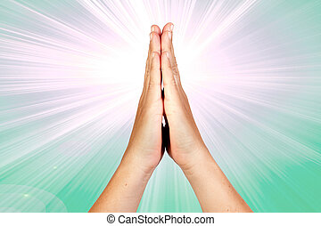 Hands clasped in prayer with rays of light on green...