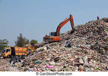 Backhoe at garbage dump - Backhoe moves trash in a landfill...