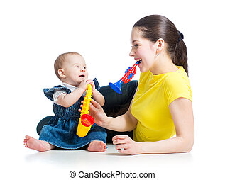 Mother and baby girl having fun with musical toys. Isolated...
