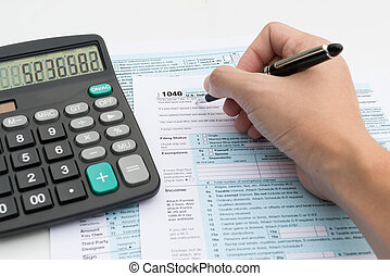 Income tax - Filling out income tax forms with calculator...