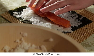 Making sushi rolls with salmon and philadelphia cheese.